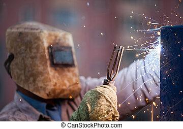 Arc welder worker in protective mask welding metal...