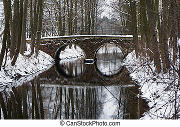 Arch bridge in snowy winter park. - Foot arch bridge and its...