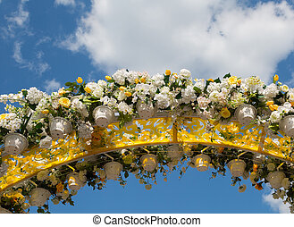 Arch, decorated with artificial flowers, on a background of blue sky