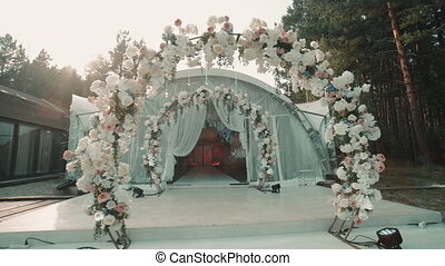 Arch decorated with flowers and white tent standing outdoors on summer day. Motion shot of elegant chateau with blossom decor and wedding decoration stands outside in warm weather. Idyllic picture of bridal preparation with unique location and expensive details is ready for romantic celebration of ...