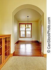 Arch doorway with empty room and wood cabinet. New luxury...