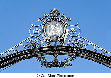 Arch on old iron gate over blue sky