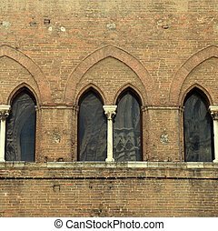 arch window at medieval brick building in the historic center of Siena, Italy.