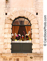 Arch window with orchids in old stone italian house
