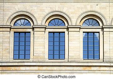 Three arch blue windows at stone building