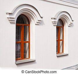 Two arch windows on a white wall.