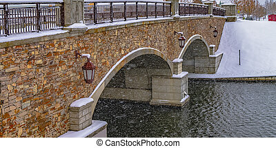 Arched bridge of a lake in Daybreak during winter