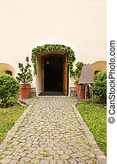Arched entrance to the restaurant and the road paved with stones
