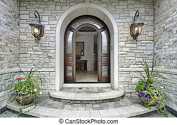 Arched stone entry to luxury home - Arched stone entry of...