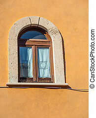 Arched window with curtains on the wall of an old house in Tivoli, Italy