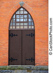 Arched wood doors in brick wall