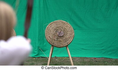 Archer holds his bow and shoots arrow at target. Archery competition, people aiming at center of the target to win the prize. Outdoor activity