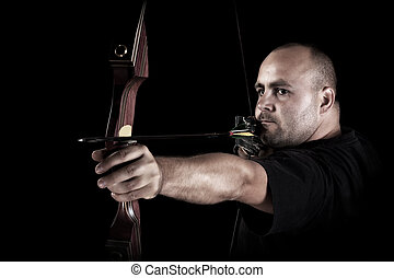 Archer in black on black background aiming with bow and...