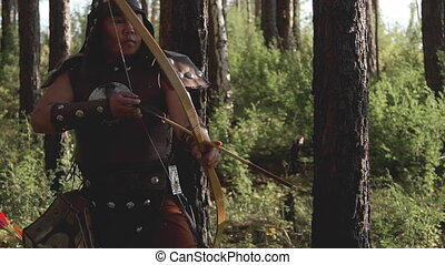 Archer with an eastern appearance aiming an arrow in forest....