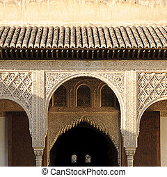 """Arches and columns carved and decorated inside the Nasrid Palace (""""Palacio Nazaries""""), part of the complex of the Alhambra in Granada, Spain"""