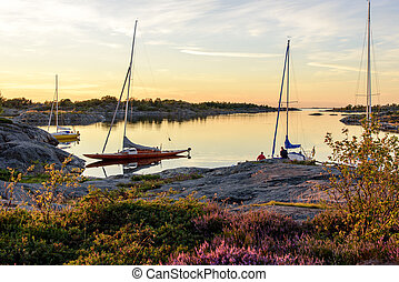 Archipelago harbour - Sunset light over sailboats moored at...