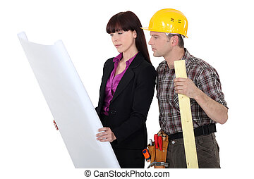 Architect and a carpenter looking at plans