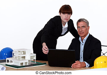 Architect and assistant working on housing project