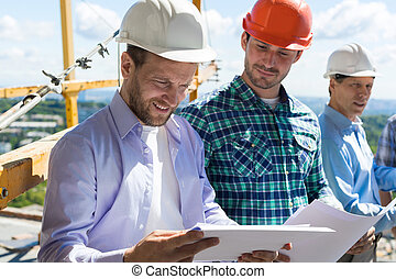 Architect And Builders Looking At Buiding Plan Blueprint Wearing Hardhat While Meeting On Construction Site