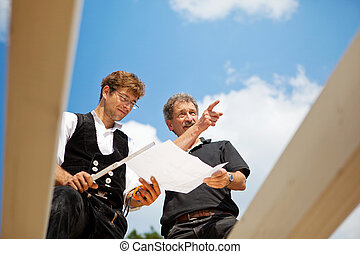 Architect and carpenter discussing the plans - Architect and...