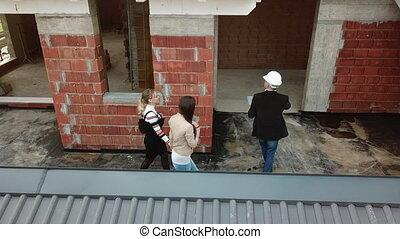 Architect And Clients Buying New Home In Construction Site -...