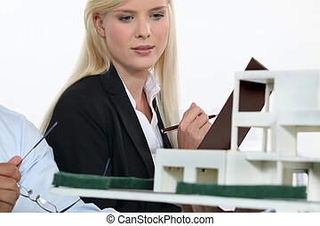 Architect and co-worker looking at model building