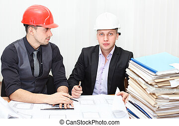 Architect and construction engineer discussing plan in office room