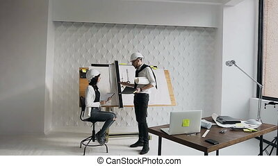 Architect and engineer discuss important work questions on the construction of a residential building on a construction site near a drawing instrument with a project
