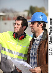 Architect and foreman looking at plans