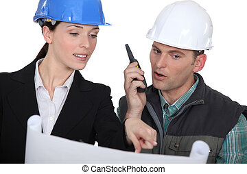 Architect and foreman with a walkie talkie