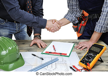 Architect and young electrician technician shake hands in front of a residential building project