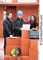 Architect and young family visiting house plot