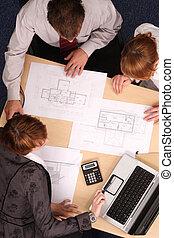 Architect, clients, blueprints - Architect showing couple of...