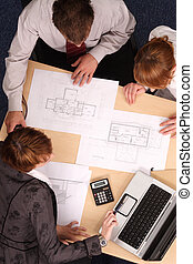 Architect, clients,blueprints - Architect showing couple of...