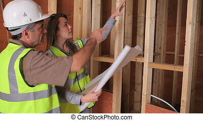 Architect discussing construction plan with builder in construction site