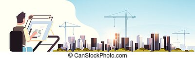 architect drawing blueprint urban building plan on adjustable board over city construction site tower cranes residential buildings cityscape sunset skyline background horizontal portrait