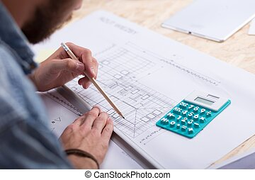Architect estimating project cost - Architect with blueprint...