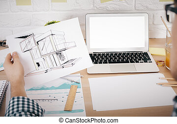 Architect evaluating his construction project at office desk with blank white laptop, business report and stationery items. Mock up
