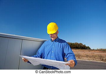 Architect Examining Blueprint Against Clear Sky - Mature...