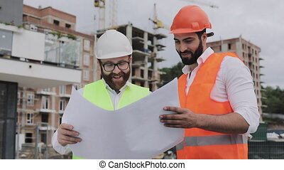 Architect expert engineers talking and analyze design plan standing under construction site. Professions, construction, workers, architect concept. Slow motion.