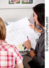 Architect Explaining Blueprint To Client