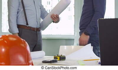 Architect gives a roll of building plans to his colleague