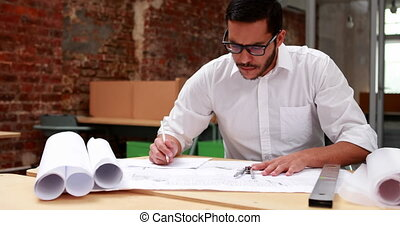 Architect going over blueprints - Young architect going over...
