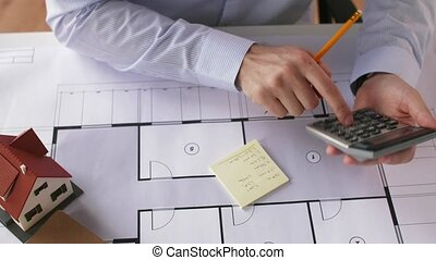 architect hand with blueprint and calculator