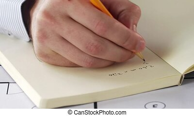 architect hand with blueprint writing to notebook