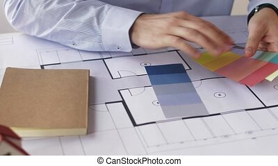 architect hands with blueprint and color palettes