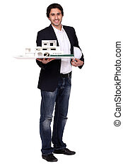 architect holding a helmet and a model of a house