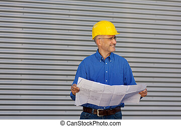 Architect Holding Blueprint While Looking Away Against Shutter