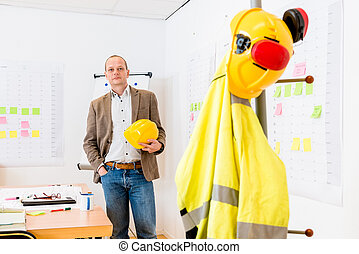 Architect Holding Hardhat At Office
