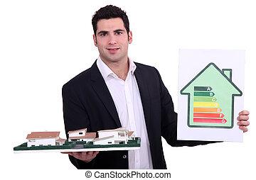 Architect holding model housing and energy rating panel